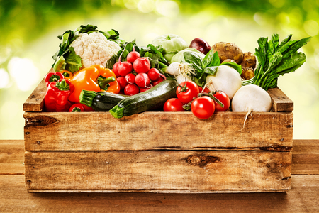 Wooden crate of farm fresh vegetables with cauliflower, tomatoes, zucchini, turnips and colorful sweet bell peppers on a wooden table outdoors in sparkling sunlight on greenery