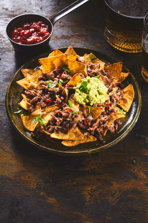 NACHO: Red salsa hot sauce in bowl beside large ceramic plate of yellow corn tortilla chips, guacamole and beer on dark wooden table with copy space