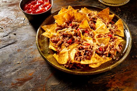 red cooked: Plate full of yellow corn tortilla chips, melted cheese and cooked ground beef with bowl of red salsa in background over wooden table with copy space Stock Photo