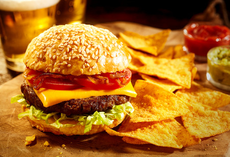 chips and salsa: Large sesame seed bun cheeseburger topped with tomatoes, onions and lettuce with nacho chips, salsa, guacamole and beer in background