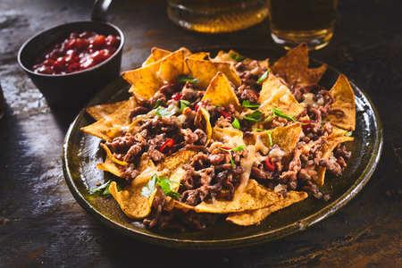 tortilla de maiz: chips de tortilla con guarnición de carne molida, queso fundido, pimientos y hojas de cilantro en la placa sobre la mesa de madera Foto de archivo