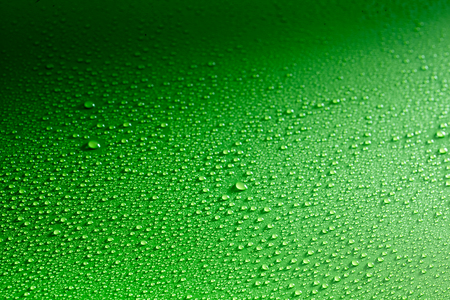 impregnated: Gradient background with rain drops spread across shiny green surface and lit from one side Stock Photo