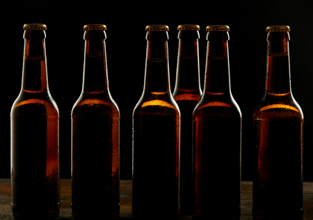shadowy: Branding and marketing concept for beer with a line of unopened unlabelled full blank brown bottles on a dark shadowy background conceptual of Oktoberfest or nightlife