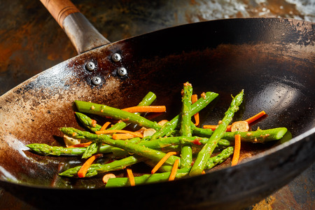 tilted view: Sauteed mix of fresh asparagus shoots and carrots in an old grunge frying pan in a close up tilted angle view