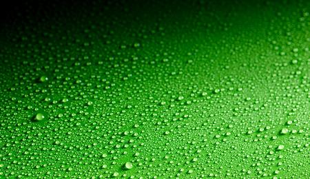 Oppervlakte gemaakt van close-up uitzicht op dauw druppels verspreid over een glanzend groen oppervlak