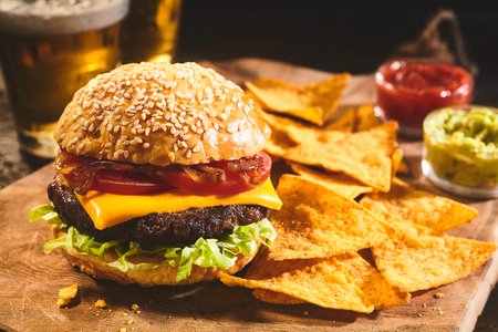 tortillas: Large freshly prepared cheeseburger topped with tomatoes, onions and lettuce with nacho chips, salsa, guacamole and beer in background