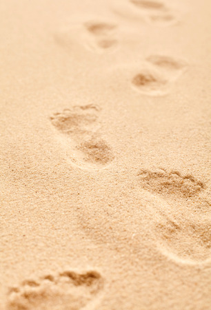 castaway: Bare footprints receding away from the camera on golden coarse beach sand with focus to the pair in the foreground conceptual of a summer at the seaside