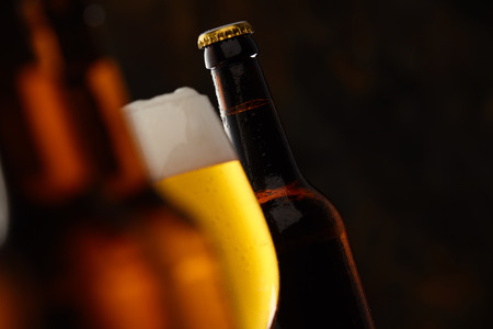 tilted view: Glass of glowing golden frothy beer in a selective focus view between to beer bottles with copy space for Oktoberfest, tilted angle perspective