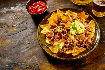 NACHO: Delicious plate of yellow corn tortilla chips with cheese, meat, guacamole and red hot spicy salsa over table with copy space