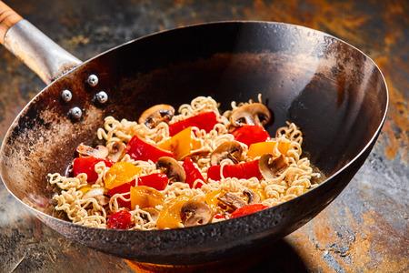 Heerlijke noedels en plantaardige roerbak chinese wok gekookt in olie gekleurd pan tegen een rustieke achtergrond Stockfoto