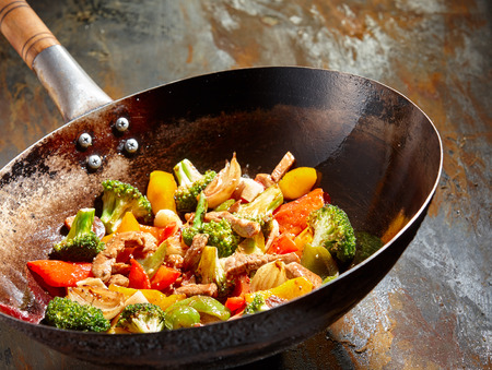 black dish: Tasty vegetable dish with broccoli and colorful peppers cooked in oil stained asian wok recipe against a rustic background