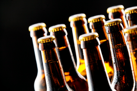 Meerdere koud ongeopende bierflesjes in een taverne of pub in een close-up het oog op hun nek en tops over een zwarte achtergrond conceptueel van het Duitse Oktoberfest Stockfoto