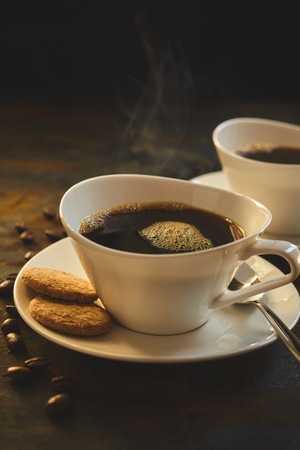 energising: Two fresh servings of hot espresso with cookies on porcelien saucer besides loose coffee beans