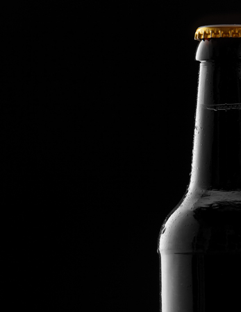 unlabelled: Partial cold sealed full beer bottle with condensation as a side border over a black background with copy space for your Oktoberfest advertising
