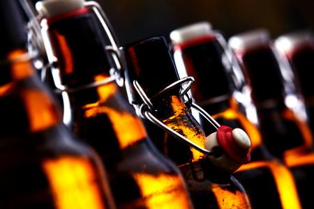 Rij van bierflesjes gloeien in het donker Stockfoto