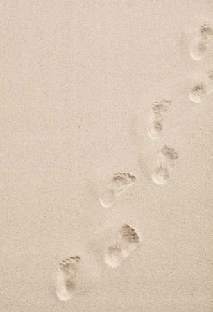 Line of footprints in smooth white desert or beach sand crossing diagonally through the frame in a conceptual overhead view with copy space Standard-Bild