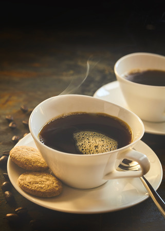 energising: Close up of freshly brewed black coffee by beans and two delicious cookies all placed on a rustic table