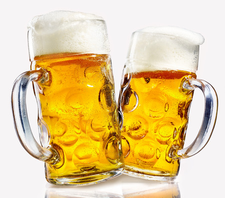 Two glass beer mugs full of golden lager with thick frothy heads over a reflective white background conceptual of the Oktoberfest
