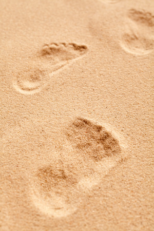 clue: Close up on a bare footprint in granular golden beach sand conceptual of summer vacations, clue in a crime or recreational solitude
