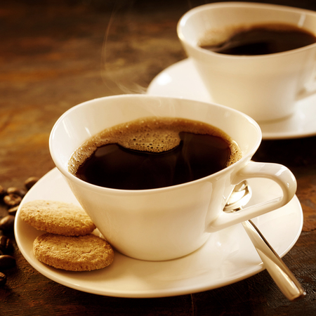 addictive drinking: Freshly brewed cup of strong espresso coffee with cookies served in a stylish modern white cup and saucer with a second cup behind in square format