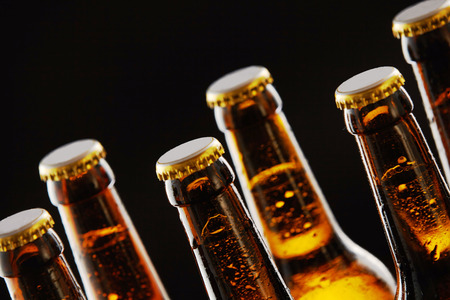 unlabelled: Necks of sealed beer bottles with condensation in a close up view over a black background in a tilted angle view conceptual of Oktoberfest