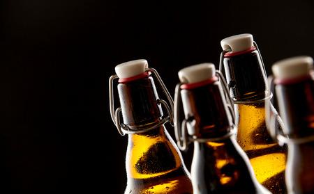 Ijskoud bier verzegelde flessen in een close-up van de nek op een zwarte achtergrond met een kopie ruimte voor uw Oktoberfest reclame