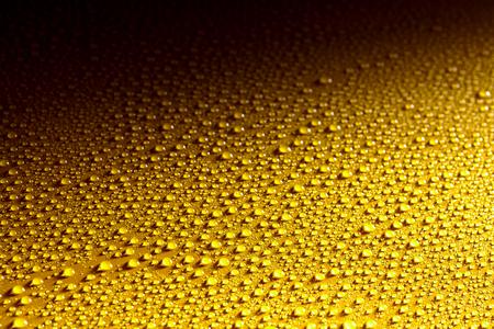 雨、露、霧または暗い影付きの背景としぶきから輝く澄んだきれいな水に濡れた黄色金属面を削除します。
