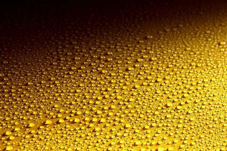 어두운 그림자 배경으로 비, 이슬, 안개에서 맑고 깨끗 한 물 방울 반짝이 또는 튀는 젖은 노란 금속 표면 스톡 콘텐츠