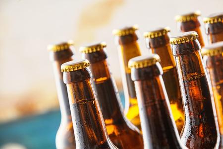 Gekühlte erfrischendes Bier auf einen Zähler in einer Bar oder Kneipe mit Nahaufnahme Fokus auf den Hälsen und ungeöffnet Spitzen stehend und Kopie Raum konzeptionell von der Wiesn feiern Standard-Bild - 58460343
