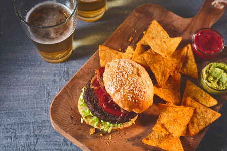 chips and salsa: Cropped view on freshly cooked burger in sesame bun, tortilla chips, salsa and guacamole on cutting board with beer on table Stock Photo