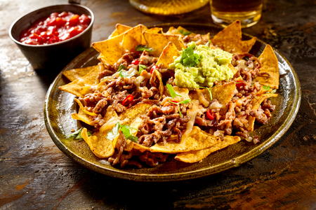 melted cheese: Yellow corn nacho chips garnished with ground beef, guacamole, melted cheese, peppers and cilantro leaves in plate on wooden table