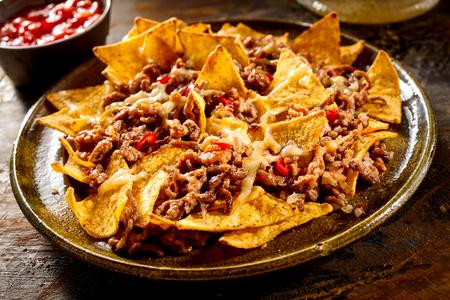 terreno: Piatto pieno di nachos mais giallo e carne macinata cotta con ciotola di salsa rossa in background sul tavolo di legno