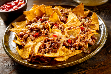 ground: Plate full of yellow corn nachos and cooked ground beef with bowl of red salsa in background over wooden table Stock Photo