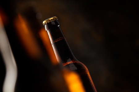 tilted view: Tilted angle view of an unopened unlabelled glowing beer bottle with selective focus and shadowy dark copy space conceptual of a tavern and Oktoberfest