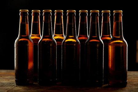 unlabelled: Group of sealed unlabelled brown beer bottles standing on a wooden counter in a concept of the Oktoberfest or for branding and advertising