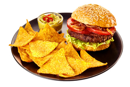burger: Isolated round black plate of nacho tortilla chips, guacamole and hamburger topped with tomatoes and friend onions in sesame seed bun over white background