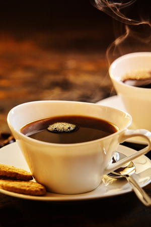 energising: Close up on two servings of delicious hot coffee with spoon and biscuits in porcelain saucer Stock Photo