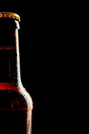 botellas de cerveza: el hielo no marcado botella de cerveza fría parcial individual como una frontera sobre un fondo negro con copia espacio para la Oktoberfest
