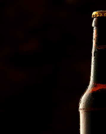 unlabelled: Cold frosted beer bottle border with a partial view of a sealed full bottle of lager or beer over a black background with copy space Stock Photo