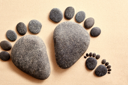 Top down view on pair of smooth stones in the shape of adult and baby human feet partially covered in yellow sand