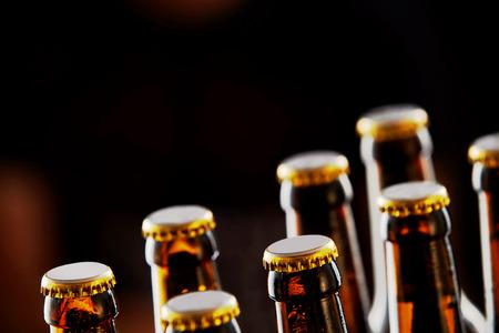 Dos hileras de botellas de cerveza marrones sin abrir en una vista en diagonal primer sobre un fondo oscuro con espacio de copia Foto de archivo