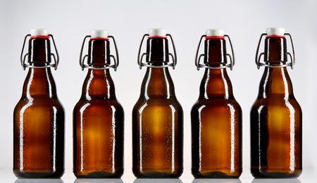 abreast: Straight on view of five blank glass bottles of beer for Oktoberfest or other concept regarding alcohol sales and branding