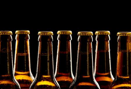 Fila de las botellas de cerveza marrones sin abrir refrigerados en una vista de cerca de los cuellos y las tapas sobre un fondo negro conceptual de Oktoberfest