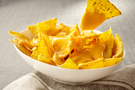 pulled over: Single triangular yellow corn tortilla chip pulled out of bowl of cheese covered nachos over gray and white tablecloth