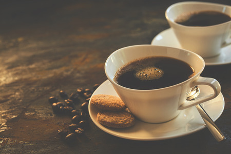 brew: Two cups of expresso served in classy ceramic mugs beside cookies and a handful of coffee beans