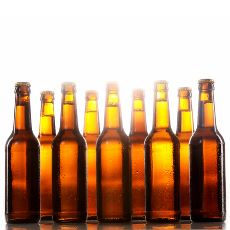 unlabelled: Tall beer bottles with no labels and metal caps stand two rows deep against a white background