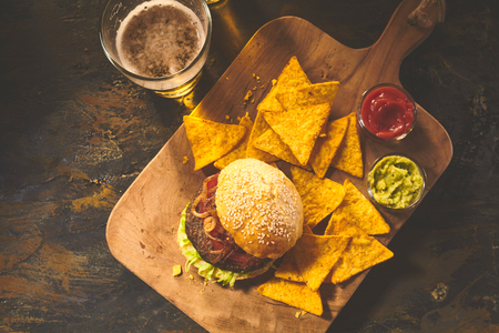 Top down view on burger in sesame bun, tortilla chips, salsa and guacamole on cutting board with beer on table Stock Photo