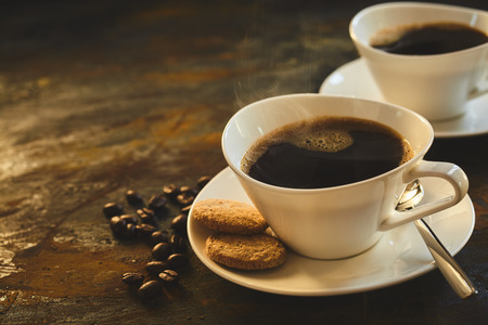 Cup of aromatic fresh hot steaming espresso coffee in an elegant white porcelain cup and saucer served with two crunchy biscuits on a rustic wooden table with coffee beans Stock Photo