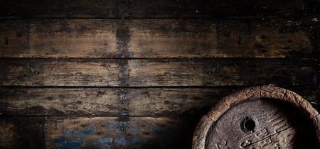 Altes Eichenbier-, Wein- oder Brandyfass über einer verwitterten strukturierten Holzwand in einem Keller oder in einer Taverne im Panorama-Bannerformat mit Kopienraum