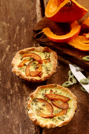 pastry crust: Appetizing small butternut, leek and custard quiches with a crispy pastry crust on a rustic wooden kitchen table with fresh ingredients, high angle view